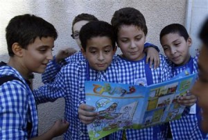 "Children read an edition of the ""Qaws Quzah"" (Rainbow) magazine, in Tunis"