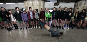 """Passengers, not wearing pants, perform as they wait for a subway train during the """"No Pants Subway Ride"""" in Prague"""