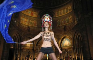 Topless activist of women's rights group Femen holds a European flag as she demonstrates inside Strasbourg's Cathedral on the eve of Pope Francis' visit to European institutions, in Strasbourg