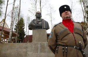 Leader of Orthodox Cossack Union Polyakov stands next to a bust of Russian President Putin during its unveiling ceremony in Leningrad region