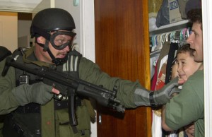 IMPROVED CROPPED _ In this third of seven sequential photos, fisherman Donato Dalrymple holds 6-year-old Elian Gonzalez inside the bedroom of Lazaro Gonzalez during the pre-dawn hours Saturday, April 22, 2000, as Border Patrol agents stormed the Miami home to seize custody of the  boy.  (KEYSTONE/AP Photo/Alan Diaz)    === ELECTRONIC IMAGE ===