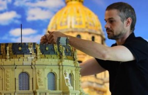 """A Lego designer creates in Lego bricks a replica of Paris' Dome des Invalides, former French emperor Napoleon Bonaparte's tomb, during a press preview of the """"History in Bricks"""", an exhibition recreating in Lego Bonaparte's life, as part of the 200th anniversary commemoration of The Battle of Waterloo, in Waterloo, Belgium, on May 29, 2015. The exhibition, created by Eric Jousse,  will run May 30-July 31, 2015 in coordination with the reenactement of the battle on June 19-20, 2015, which led to the fall of Napoleon.  AFP PHOTO/EMMANUEL DENAND"""