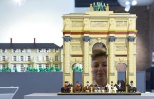 A woman poses for photographers behind a model of the The Arc de Triomphe du Carrousel, made with 10,000 Lego bricks in 90 hours, in Waterloo, Belgium May 29, 2015. The exhibition, which used around one million Lego bricks, is held as part of the commemorations of the bicentenary of the Battle of Waterloo. REUTERS/Yves Herman