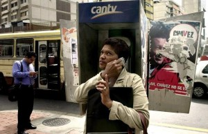 A woman uses her mobile phone next to some telephone booths of the Venezuelan telecom company CANTV, still decorated with electoral propaganda from the past december elections supporting Hugo Chavez, Tuesday 09 January 2007, in Caracas. The reelected president Hugo Chavez said yesterday `we have to nationalize what was privatized´, refering to the Venezuelan telecom company CANTV.  EPA/CHICO SANCHEZ