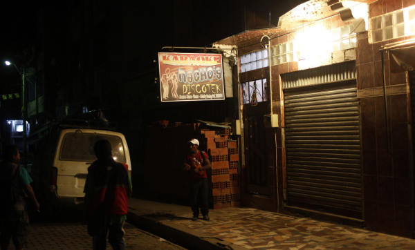 """In this June 6, 2015 photo, a man walks past a closed karaoke and discoteque in La Asunta, northeast of La Paz, Bolivia. At night groups of citizens patrol the town of 7,000 people, after neighborhood organizations along with police and city council ordered a """"dry law"""" for a month hoping to end a series of rapes and other crimes. (AP Photo/Juan Karita)"""