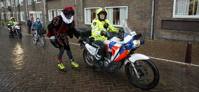 2014-11-16 13:20:59 AMSTERDAM - Een Zwarte Piet op rolschaatsen hangt achter een politiemotor tijdens de intocht van Sinterklaas. ANP BART MAAT