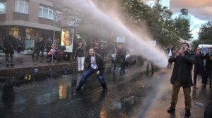 Riot police use a water cannon as they confront protesters near the headquarters of a media company with alleged linked to a government critic, where police enforced a court order to seize the business, in Istanbul, Oct. 28, 2015.  Police in Istanbul carried out the dawn raid at the building, using tear gas and water canons during confrontations with protesters,  Critics denounced the action as a government crackdown on opposition voices ahead of the Nov. 1 election. (Usame Ari / Cihan News Agency via AP) TURKEY OUT