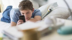 Teenage-boy-16-17-lying-on-bed-and-text-messaging