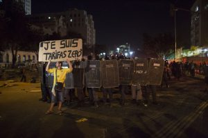 """A protester standing in front of police officers holds a sign that reads """"Je Suis Zero Fair"""" during a march against bus fare hikes in Rio de Janeiro, Brazil, Friday, Jan. 8, 2016. The march, which is also taking place in other Brazilian capitals, began peacefully in downtown Rio de Janeiro but turned violent. (AP Photo/Felipe Dana)"""