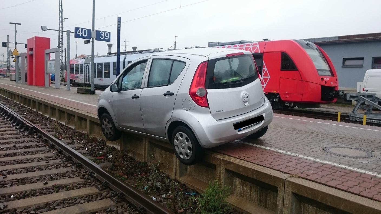 Ein Auto hängt mit den beiden linken Reifen von einer Bahnsteigkante in Richtung Gleise herunter
