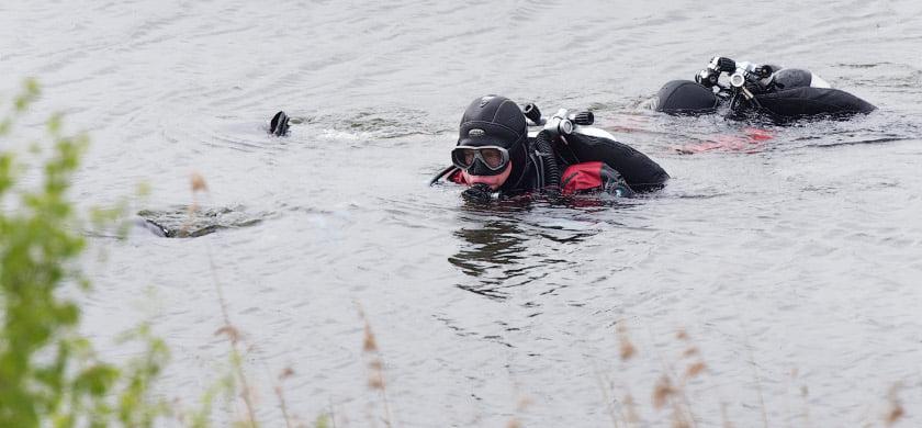 Duikers zoeken bij de afgraving in maarn naar de twee vermiste jongentjes. foto Michael Kooren/ANP