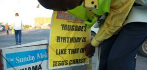 """A newspaper vendor in Harare places  a banner describing  Zimbabwean President Robert Mugabes birthday like that of Jesus Christon, in Harare, Sunday, Feb. 21, 2016. Mugabe turned 92 on Sunday making him the worlds oldest serving  President.On Friday Mugabe delivered a televised speech  warning ruling ZANU PF rival factions to end succession fights he described as """"very ugly"""" ahead of his birthday party celebrations to be held  in  the south- eastern town of Masvingo on Saturday.(AP Photo/Tsvangirayi Mukwazhi)"""