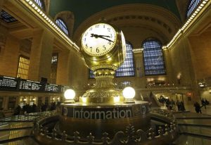 FILE- In this Jan. 9, 2013 file photo, the famous opalescent clock keeps time at the center of the main concourse in Grand Central Terminal is shown in New York.  The country's most famous train station and one of its finest examples of Beaux Arts architecture in America turns 100 on Feb. 1.  The building's centennial comes 15 years after a triumphant renovation that  removed decades of grime and decay. (AP Photo/Kathy Willens, File)