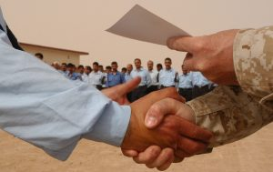 A newly-graduated Iraqi policeman receives a handshake and a certificate from Lt. Col. Daniel J. Racca, commandant of the Ar Ramadi Police Academy. A graduation ceremony was held here for 88 Iraqi policemen April 22. This was the first class instructed by Racca and his team of reserve Marines attached to 3rd Battalion, 11th Marine Regiment.  (USMC photo by Cpl. Paula M. Fitzgerald)