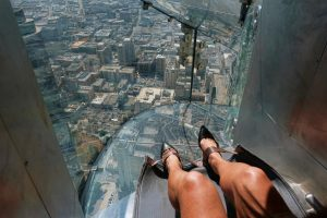 FILE - In this Thursday, June 23, 2016 file photo, a woman prepares to take a ride down a glass slide at the U.S. Bank Tower building in downtown Los Angeles. A lawsuit claims a woman suffered a broken ankle on the recently opened glass-enclosed slide attached to the exterior of a downtown Los Angeles skyscraper. The lawsuit filed Wednesday, July 13, 2016, against building owner OUE Skyspace LLC and a concession company claims negligence. (AP Photo/Richard Vogel, File)
