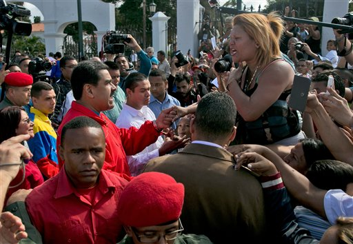 Venezuela's President Nicolas Maduro, center left, greets a supporter as he arrives to vote during congressional elections in Caracas, Venezuela, Sunday, Dec. 6, 2015. (AP Photo/Alejandro Cegarra)