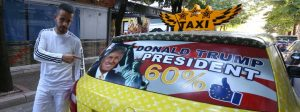 "Uljan Kolgjegja, 37, an Albanian taxi driver, points to a picture of U.S. Republican candidate Donald Trump in his car in the Albanian capital, Tirana, Monday, Sept. 26, 2016. Kolgjegja said Monday he was prompted to decorate his taxi with pictures of the Republican candidate after Albania's Prime Minister Edi Rama said Trump could be ""a real threat to Albanian-American ties."" The move has attracted attention in the capital Tirana and Kolgjegja says he is earning more money than ever before in his 13 years as a taxi driver. (AP Photo/Hektor Pustina)"