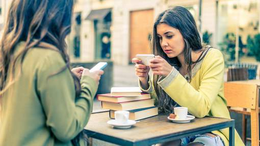 Two women sitting in a bar and staring at mobile phones - Girls watching a video online on portable device