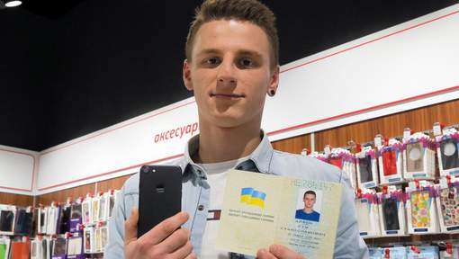 A young man shows his passport giving his name as iPhone Sim (seven), and a new iPhone 7 in an electronics shop in Kiev, Ukraine, Friday, Oct. 28, 2016. A A computer company in Kiev announced that it will give a new iPhone 7 to anybody who officially changes their name to iPhone Seven. (AP Photo/Efrem Lukatsky)